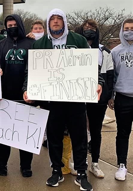 """PR Football Player holds sign without the """"H."""""""